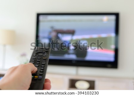 Remote control with Racing cars on TV screen