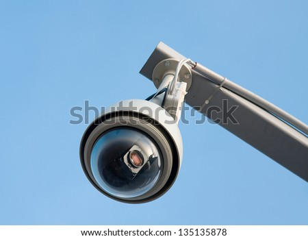 Remote controlled security camera against blue sky - stock photo