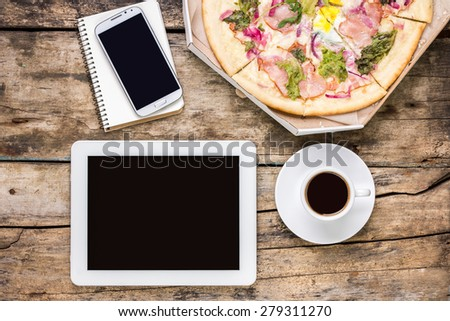 Remote freelance workplace coffee break. Outsource workspace with tablet PC, smartphone and pizza with coffee. Top view image - stock photo