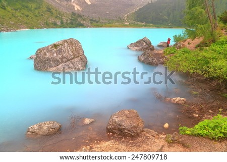 Remote hiker on the shores of Sorapis lake surrounded by huge boulders, Dolomite Alps, Italy - stock photo
