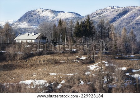 Remote house with tall mountains in the background covered with snow - stock photo