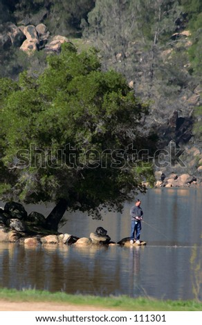 Remote lake park with fisherman. - stock photo