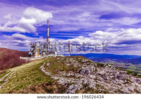 Remote mountain communications center with different antennas and towers against a deep blue sky with beautiful white clouds on top of the Nanos, Slovenia  - stock photo
