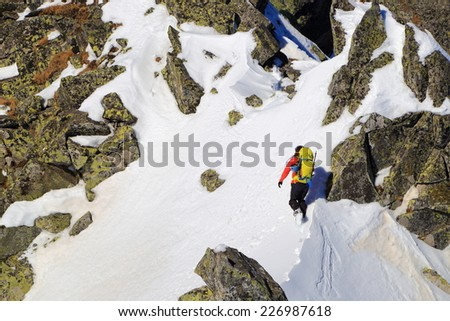 Remote mountaineer traversing an exposed mountain face covered with snow  - stock photo