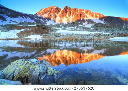 Remote summits lit by rising sun and reflected by nearby lake - stock photo