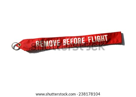 Remove before flight is a safety warning commonly seen on removable aircraft and spacecraft components, typically in the form of a red ribbon. A very important reminder before taking off into the sky - stock photo