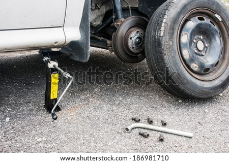 Removed wheel beside lifted car ready for change - stock photo