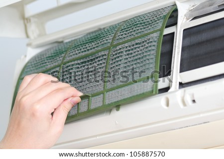 Removing dirty air-conditioner filter for washing - stock photo