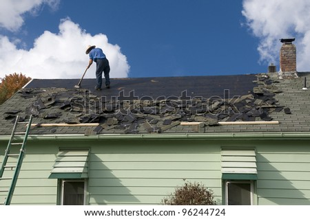 Removing old shingles to prepare a roof for a new installation with blue sky - stock photo