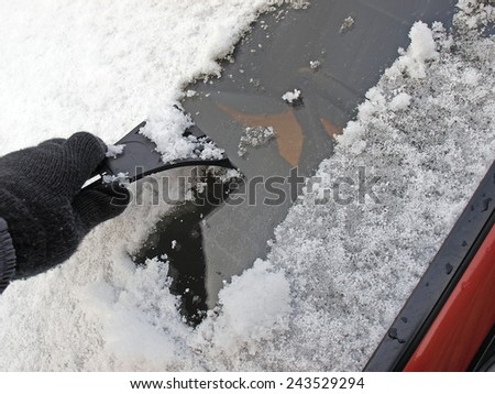 Removing snow from car window with plastic scraper         - stock photo