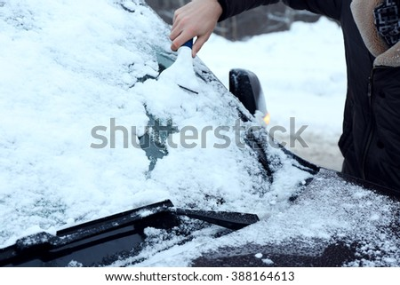 Removing snow from car windshield, closeup