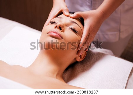 Removing stress. Beautiful young woman lying on back while massage therapist massaging her head