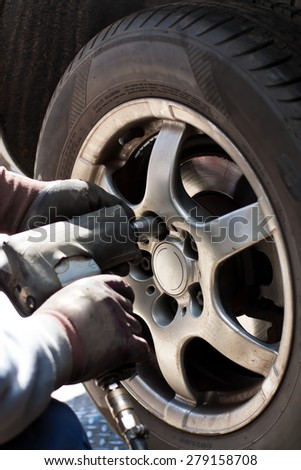 Removing the wheel of a car in the automobile repair shop. - stock photo