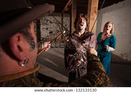 Renaissance hero yelling in sword fight with lady behind him - stock photo