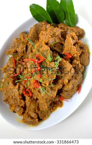Rendang - spicy delicious meat dish cooked with herbs, spices and coconut milk. served in white plate