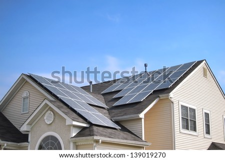 Renewable clean green energy saving efficient photovoltaic solar panels on multiple gable suburban house roof over blue sky - stock photo