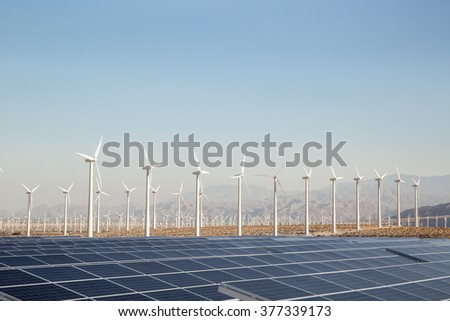Renewable Energy - Solar and Windmills Mountains in the background. Sunlight, solar panels and wind turbines. Environmental conservation and alternative power generation methods.