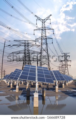 Renewable solar panels and electric power tower - stock photo