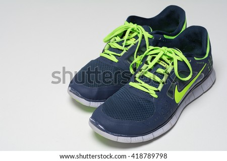 RENNINGEN, GERMANY - APRIL 30, 2016: Pair of blue green men sports shoes from Nike on white background. Nike Free