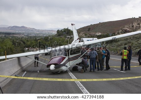RENO, NEVADA - MAY 24, 2016:  A single engine Cessna aircraft crash lands on a highway after suffering catastrophic engine failure.  No reported injuries. FAA and NTSB investigating. - stock photo