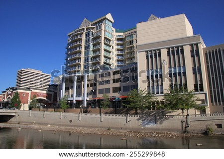 RENO, USA - AUGUST 12: Apartment buildings along Truckee river on August 12, 2014 in Reno, USA.  Reno is the most populous Nevada city outside of the Las Vegas. - stock photo