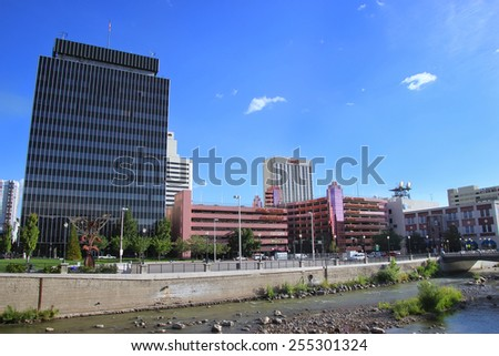RENO, USA - AUGUST 12: Apartment buildings and casinos along Truckee river on August 12, 2014 in Reno, USA.  Reno is the most populous Nevada city outside of the Las Vegas. - stock photo