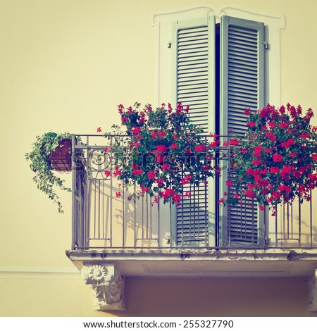 Renovated Facade of the Old Italian House with Balcony Decorated with Fresh Flowers, Instagram Effect  - stock photo