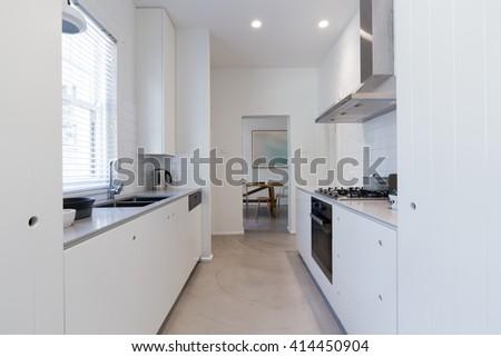 Renovated white galley style kitchen in modern Australian apartment - stock photo