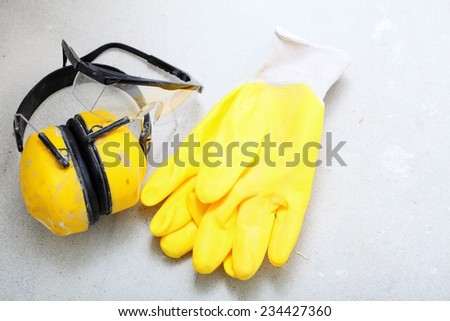 Renovation at home. Construction equipment tools work gloves yellow protective noise muffs in building site.