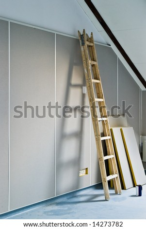 renovation - ladder and construction materials indoors - stock photo