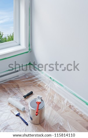 Renovations. Painting tools and floor protected by plastic. - stock photo