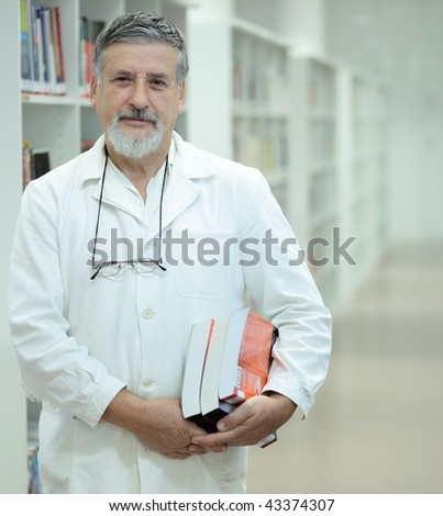 Renowned scientist/doctor in a library of research center/hospital looking confident - stock photo