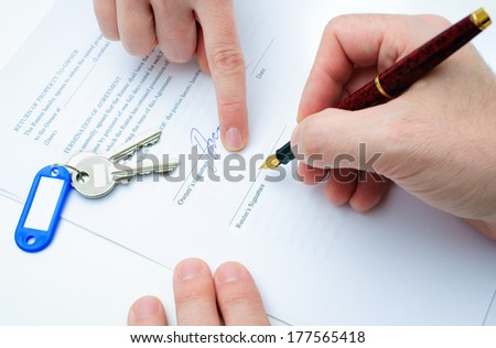 Rental agreement form with signing hand and keys and pen - stock photo