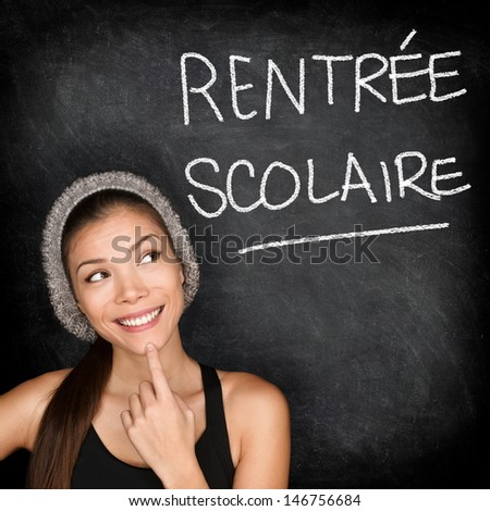 Rentr�©e Scolaire - French college university student woman thinking Back to School written in French on blackboard by female on green chalkboard. French language at college or high school. - stock photo