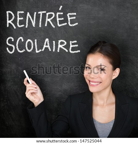 Rentree Scolaire - French teacher woman. Back to School written in French on blackboard by female on chalkboard. Woman professor teaching French language at university, high school or primary school. - stock photo
