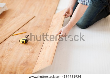 repair, building and home concept - close up of male hands intalling wood flooring - stock photo