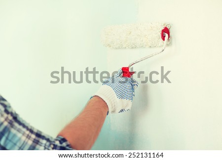 repair, building and home concept - close up of male in gloves painting wall with roller - stock photo