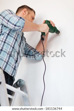 repair, building and home concept - close up of male with electric drill making hole in wall - stock photo