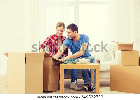repair, building and home concept - smiling couple unpacking kitchenware - stock photo