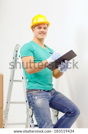 repair, building and home concept - smiling man in protective helmet with clipboard