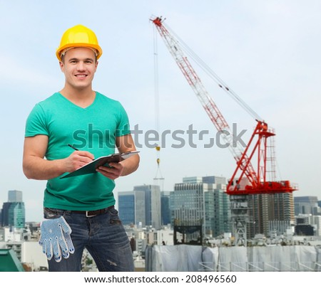 repair, building, construction and maintenance concept - smiling man in helmet with clipboard making notes