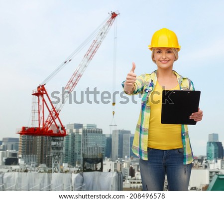 repair, building, construction and maintenance concept - smiling woman in helmet with clipboard showing thumbs up