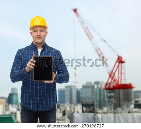 repair, building, people and maintenance concept - smiling male builder or manual worker in helmet showing tablet pc computer blank screen over city construction site background