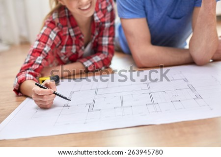 repair, building, renovation and people concept - close up of happy couple looking at blueprint at home - stock photo