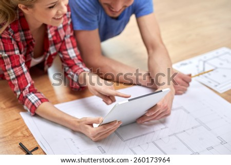 repair, building, renovation, architecture and technology concept - close up of couple with tablet pc and blueprint at home - stock photo
