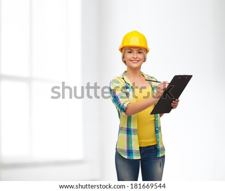 repair, construction and maintenance concept - smiling woman in helmet with clipboard