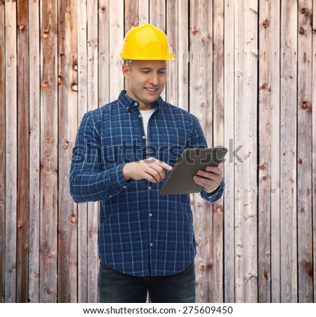 repair, construction, building, people and maintenance concept - smiling male builder or manual worker in helmet with tablet pc computer over wooden fence background - stock photo