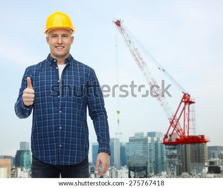 repair, construction, building, people and maintenance concept - smiling male builder or manual worker in helmet showing thumbs up over city construction site background - stock photo