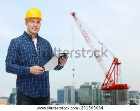 repair, construction, building, people and maintenance concept - smiling male builder or manual worker in helmet with clipboard over city construction site background - stock photo