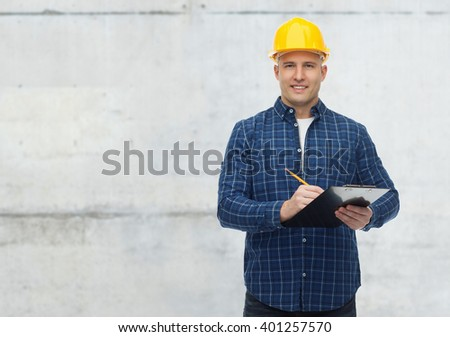 repair, construction, building, people and maintenance concept - smiling male builder or manual worker in helmet with clipboard taking notes over gray concrete wall background - stock photo